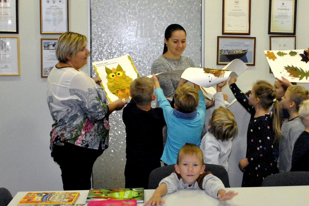 Vaikai su auklėtoja dovanoja piešinius.
