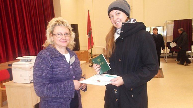 Lietuvos Konstituciją pirmą kartą balsuojančiai Emilijai Šikšniūtei įteikia Kintų rinkimų apylinkės komisijos pirmininkė Jūratė Jakienė.