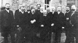 """1892 metais daryta Tilžės leidėjų nuotrauka. Iš kairės: (1) Dovas Zaunius, (6) spaustuvininkas Jurgis Aušra, (7) """"Varpo"""" ir """"Ūkininko"""" redakcijoje dirbęs kunigas Antanas Milukas, (8) prūsų lietuvių veikėjas Bendikas iš Krakoniškių, (9) Mažosios Lietuvos himno kūrėjas Jurgis Sauerveinas - Girėnas, (10) aušrininkas Martynas Jankus, (11) """"Naujosios Lietuviškos Ceitungos"""" redaktorius Mikas Kiošis."""