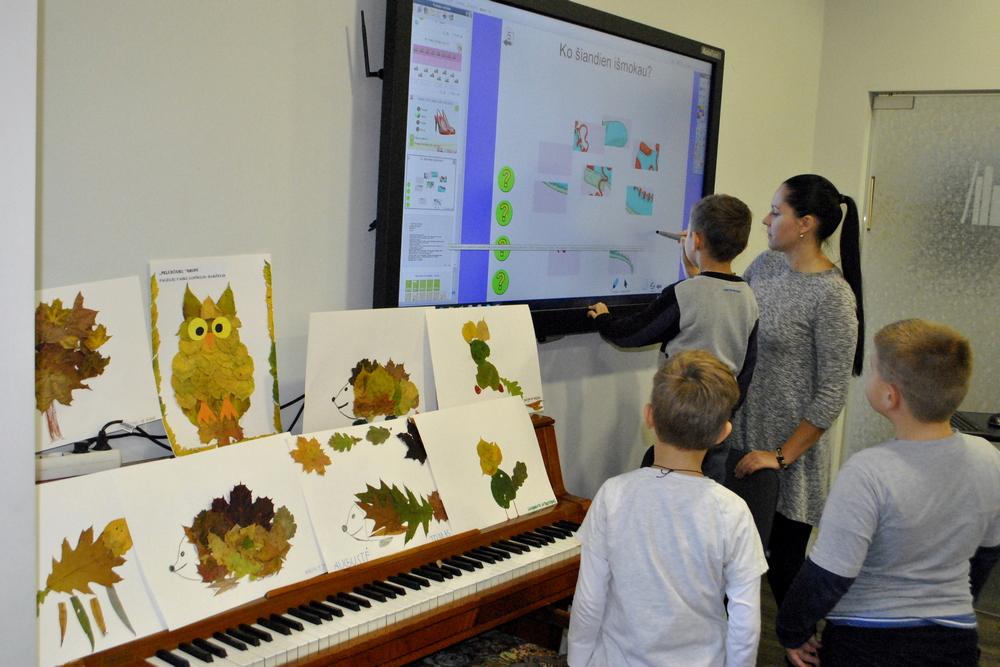 Vaikai sprendžia interaktyvią pamoką ekrane.