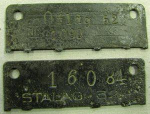 """Visiems """"Satlag Luft VI"""" karo belaisviams buvo išduodami metaliniai identifikaciniai ženklai """"dog tags"""", kuriuose buvo įrašyti kalinių numeriai. ŠHŠM, GEK 11747/1-2, IER 465/1-2"""